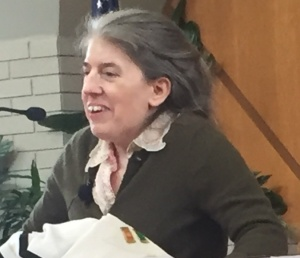 Ingrid Tischer speaking into a microphone at congregation Beth Jacob. She is a white woman with graying hair who is holding herself up with some visible effort.