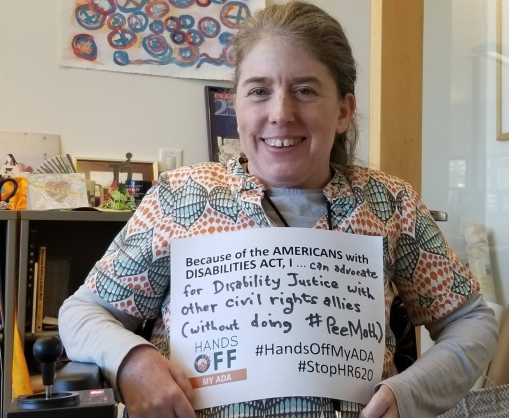 """Color photo of Ingrid Tischer, a middle-aged white cis woman, sitting in her wheelchair and smiling, golding a sign, """"Because of the Americans with Disabilities Act, I...can advocate for Disability Justice with other civilrights allies (without doing #PeeMath). #HandsOffMyADA #StopHR620"""
