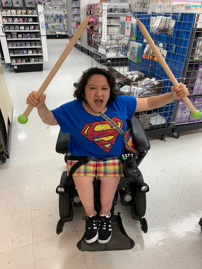 Sandy Ho, an Asian American woman with dark curly hair sits in a black power wheelchair. She is wearing a blue tshirt with a superman logo, she also has brightly colored plaid shorts on and black sneakers. Her facial expression is one of outraged protest and in both upraised fists she holds oversized wooden knitting needles.