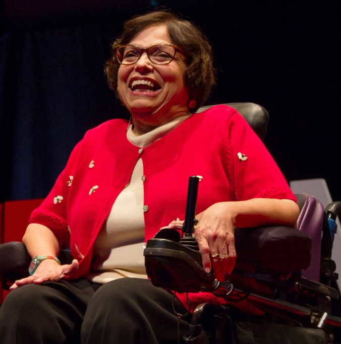 Photo of Judy Heumann in her powerchair, laughing