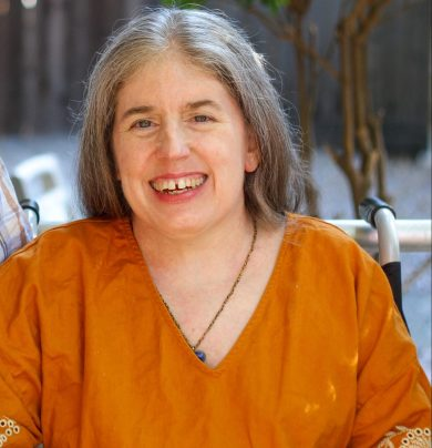 Ingrid,a middle-aged White woman with long graying hair, sitting in a wheelchair and smiling